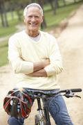 Senior man riding bicycle in park - stock photo