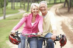 Senior couple riding bicycle in park - stock photo
