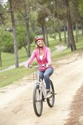 Senior woman riding bicycle in park Stock Photos