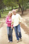Senior Couple enjoying walk in park - stock photo