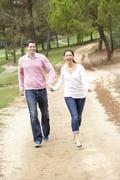 Couple enjoying walk in park Stock Photos