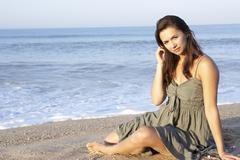 Woman sitting on beach relaxing Stock Photos