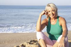 Senior woman sitting on beach relaxing - stock photo