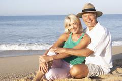Senior couple sitting on beach relaxing Stock Photos