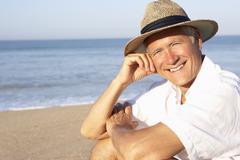 Senior man sitting on beach relaxing Stock Photos