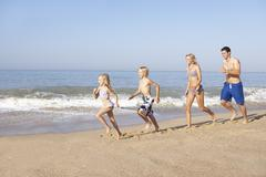 Young family running on beach Stock Photos