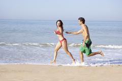 Young couple running on beach Stock Photos