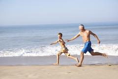 Grandfather chasing young boy on beach - stock photo