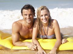 Young couple on beach holiday Stock Photos