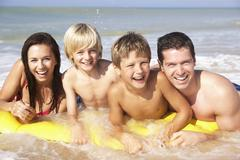 Young family pose on beach Stock Photos