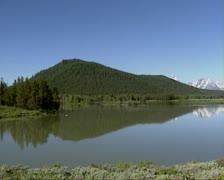 Oxbow bend lake - pan Grand Teton mountain range Stock Footage