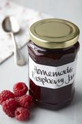 A still life of raspberry jam in jar - stock photo