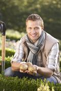 Young man posing with potatoes in garden Stock Photos