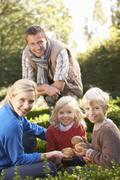 Young family sit together in garden Stock Photos