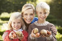 Young mother and children in garden pose with vegetables Stock Photos