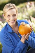 Young woman posing with pumpkin in garden Stock Photos