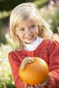 Young girl posing with pumpkin in garden Stock Photos