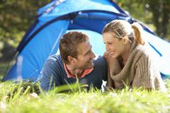 Young couple posing outside of tent - stock photo