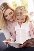 Woman and child reading together Stock Photos