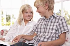 Two young children read together - stock photo
