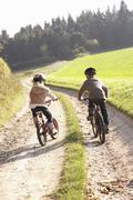 Two young children ride bicycles in park Stock Photos