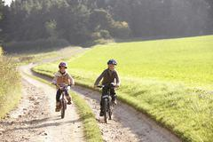 Two young children ride bicycles in park - stock photo