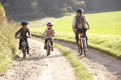 Young father with children ride bikes in park Stock Photos