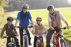 Young family pose with  bikes in park Stock Photos