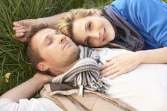 Young couple lying together on grass - stock photo