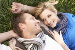 Young couple lying together on grass Stock Photos