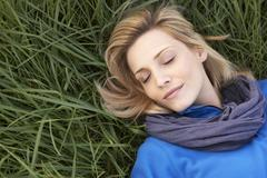Young woman napping alone on grass - stock photo