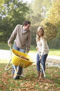 Young couple raking autumn leaves in garden Stock Photos