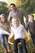 Family having fun with autumn leaves in garden Stock Photos