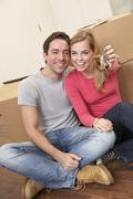 Young couple sit on the floor around boxes holding key in hand Stock Photos