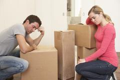 Stock Photo of Young couple looking upset among boxes