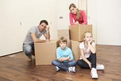 Young family looking upset among boxes - stock photo