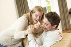 Young couple having fun laughing on sofa Stock Photos