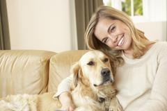 Young woman with dog sitting on sofa Stock Photos