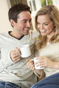 Young couple sitting and relaxing on sofa with cup in hand - stock photo