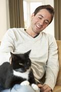 Happy young man with cat sitting on sofa - stock photo