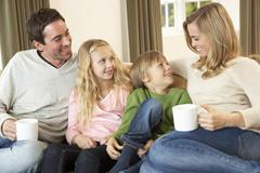 Happy young family sitting and talking on sofa Stock Photos