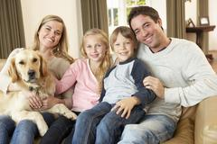 Happy young family sitting on sofa holding a dog Stock Photos