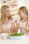 Young woman with child splitting pea in kitchen - stock photo
