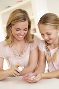 Mother putting sanitizer on young girl's hands Stock Photos