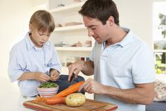 Stock Photo of Happy young man with boy peeling vegetables in kitchen