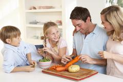 Happy family peeling vegetables in kitchen - stock photo