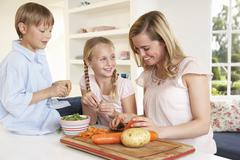 Young mother with children peeling vegetables in kitchen Stock Photos