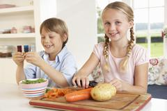 Happy children peeling vegetables in kitchen Stock Photos