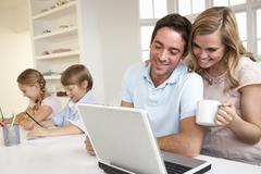 Happy young family looking and reading a laptop computer Stock Photos