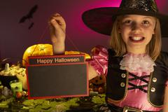 Halloween party with a child holding sign in hand - stock photo
